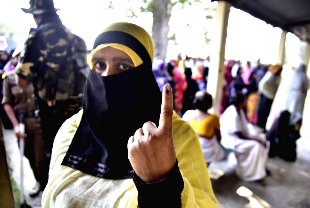 Nagaon: A muslim woman shows her inked finger after casting vote for Lok Sabha election in Nagaon District of Assam on April 11, 2019. (Photo: IANS)