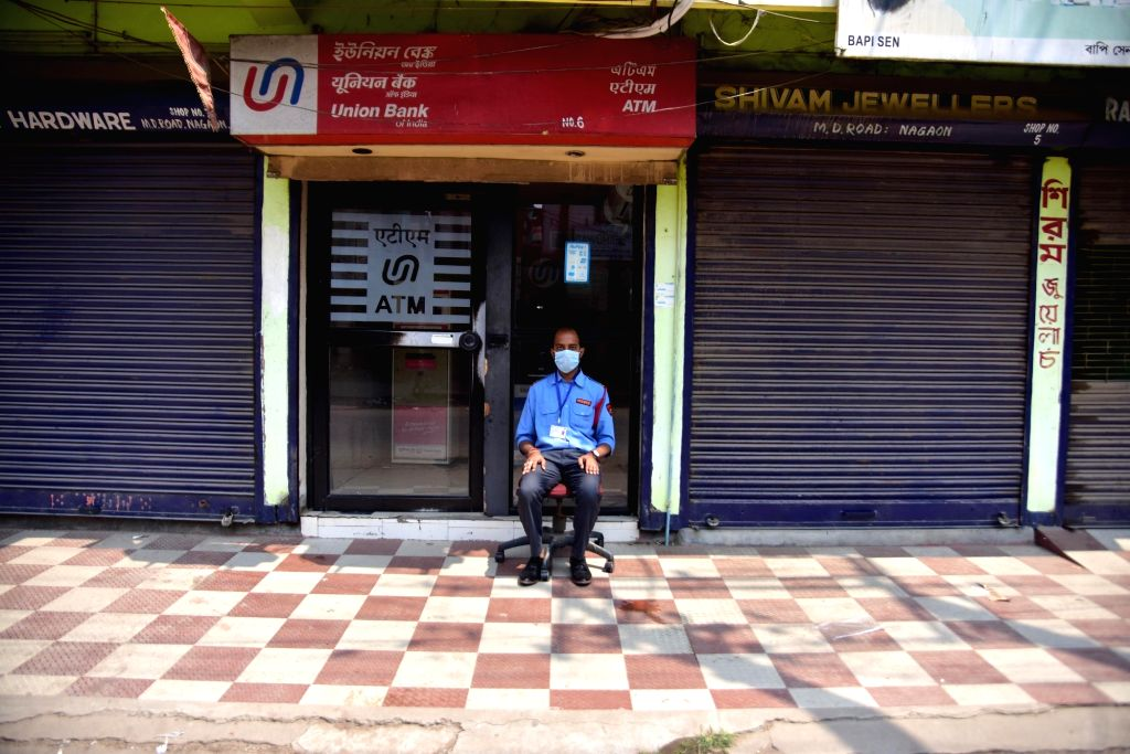 Nagaon: A security personnel wearing a mask sit-guards an ATM during the 21-day lockdown imposed across the country in the wake of COVID-19 pandemic, in Assam's Nagaon district on March 25, 2020. (Photo: IANS)