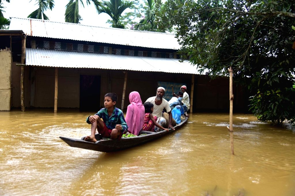 Nagaon: Villagers sail through the floodwater to reach a safer place at Bakulguri village near Kampur in Assam's flood affected Nagaon district on May 27, 2020. (Photo: IANS)