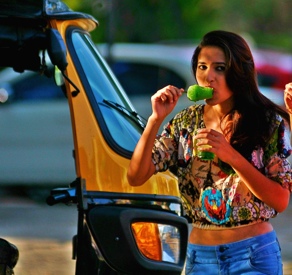 A Young girl enjoys an ice-gola (the Indian ice candy) to beat the summer heat in Nagpur, on April 4, 2015.