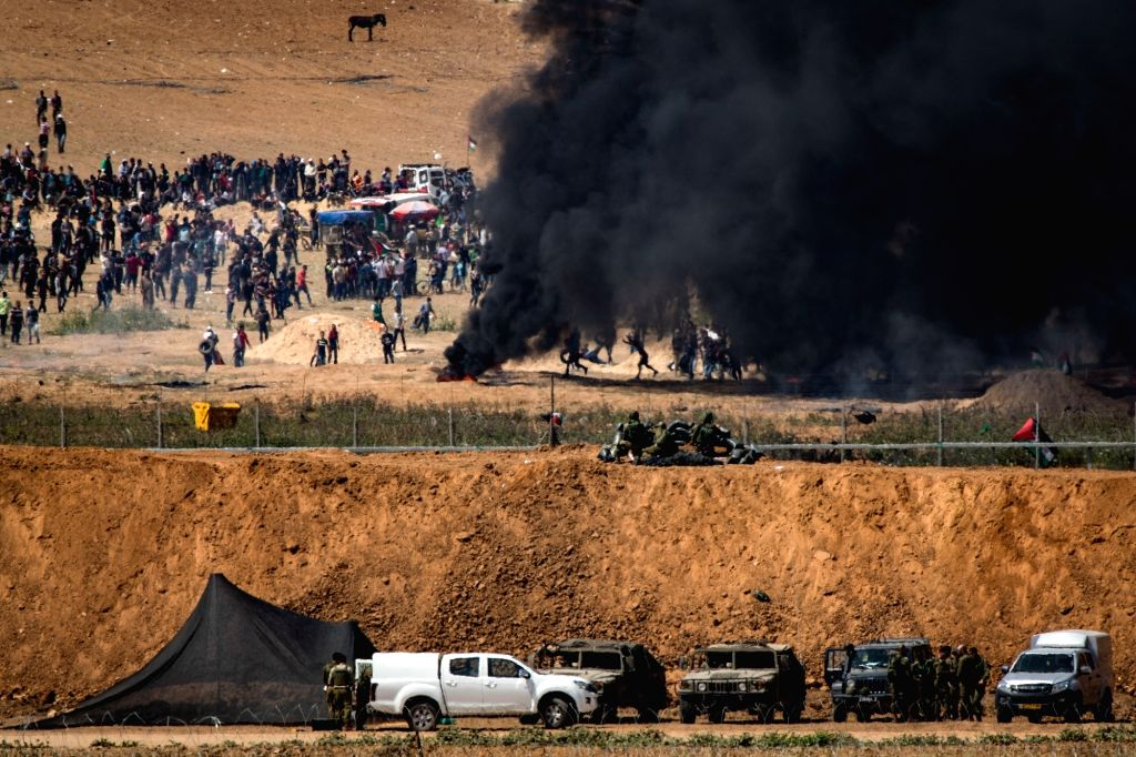 NAHAL OZ, April 6, 2018 - Palestinians protest along the barrier between Gaza and Israel near Nahal Oz, on April 6, 2018. Eight Palestinians were killed and 1,070 others injured on Friday during a ...