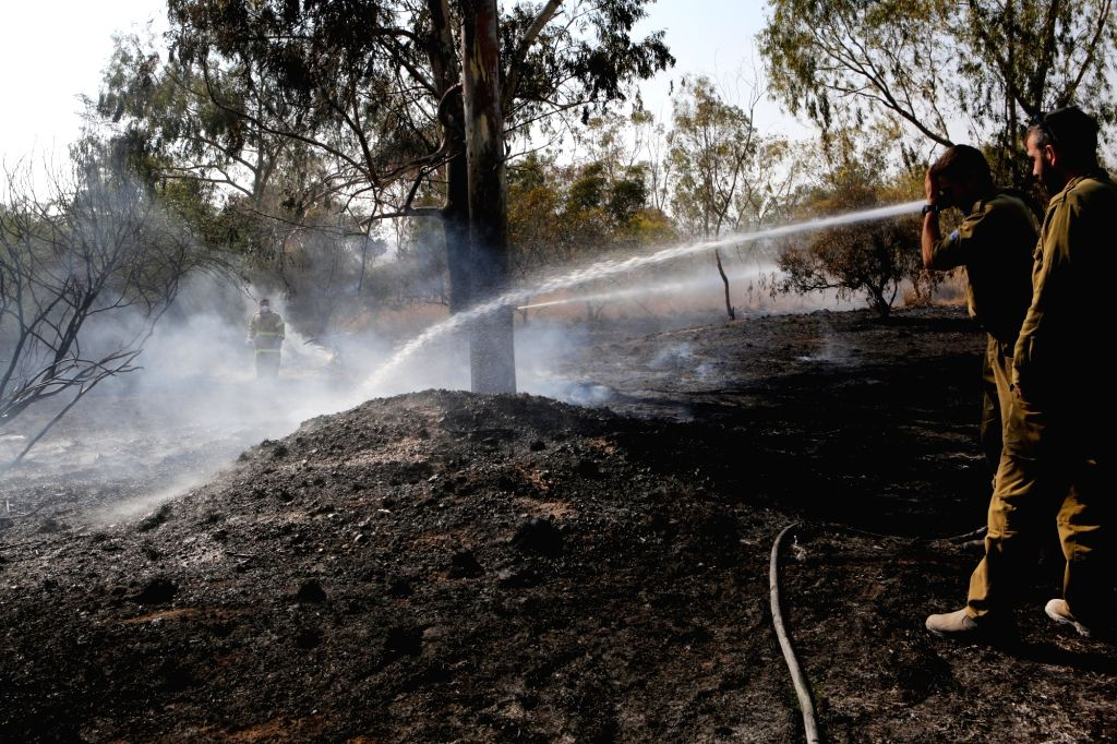 NAHAL OZ, July 18, 2018 - Israeli firefighters attempt to extinguish a fire in a forest field near the Kibbutz of Nahal Oz, near the barrier between Israel and the Gaza Strip, on July 17, 2018. The ...