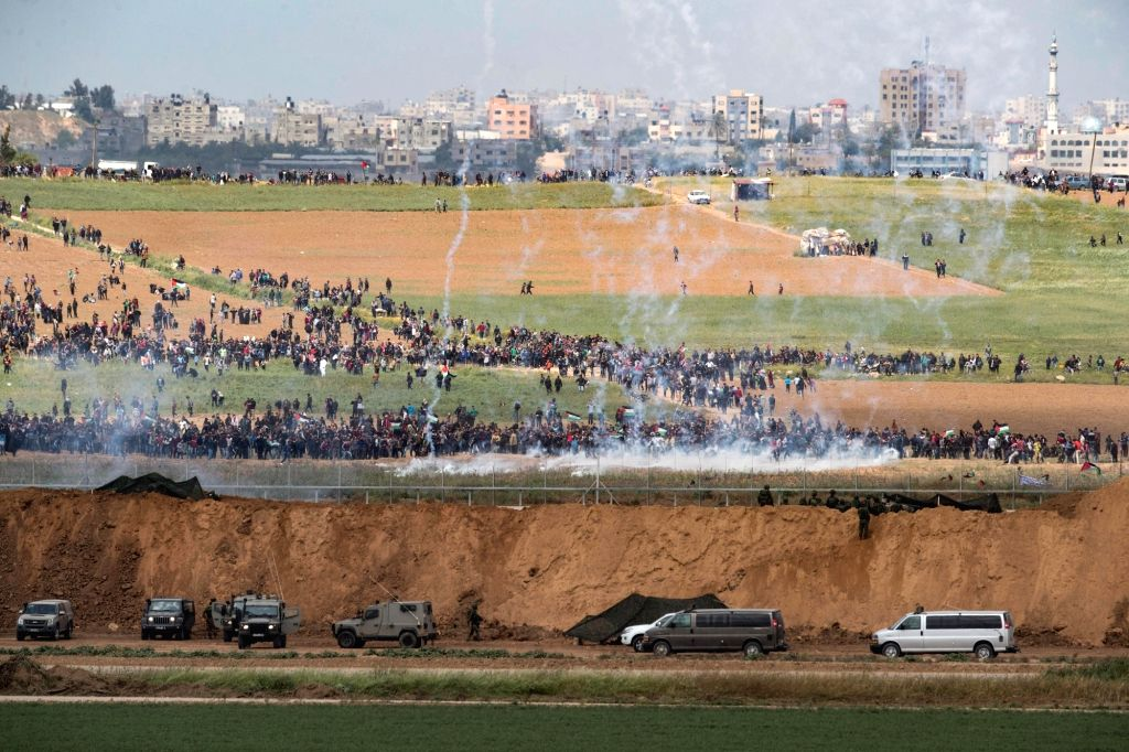 NAHAL OZ, March 30, 2018 - Palestinians protest along the barrier between Gaza Strip and Israel in Nahal Oz, on March 30, 2018. At least seven Palestinians were killed and 500 wounded Friday in the ...