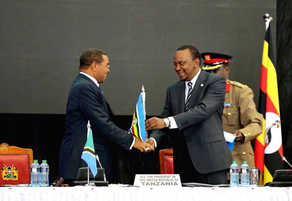 Kenyan President Uhuru Kenyatta (R) hands over the chairmanship of the East African Community(EAC) to Tanzanian President Jakaya Kikwete during the 16th EAC Heads ...