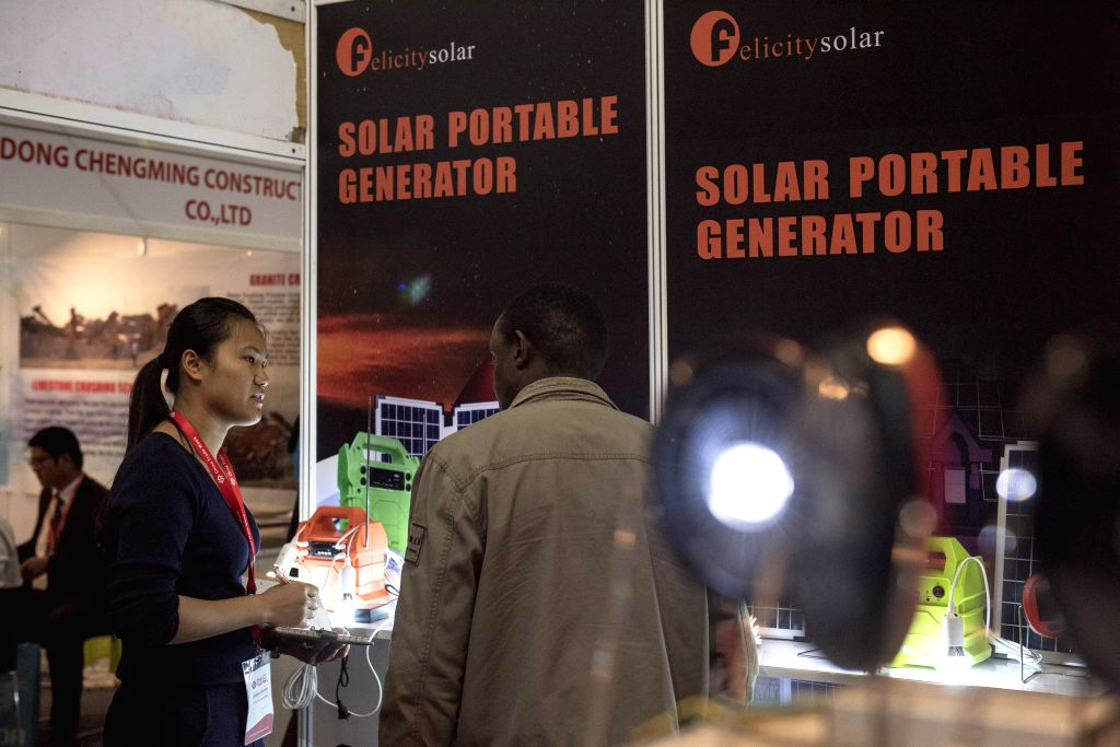 NAIROBI, June 29, 2016 - An exhibitor (L) introduces the portable solar generators to a visitor during the China Trade Week in Nairobi, Kenya, June 29, 2016. With the hope of developing African ...