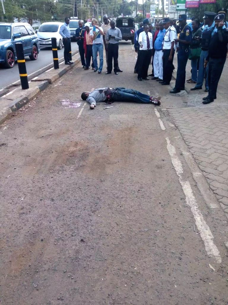 NAIROBI, Oct. 27, 2016 - People gather around the body of a man gunned down by Kenyan security officer outside U.S embassy in Nairobi, Kenya, Oct. 27, 2016. Kenya's security officer on Thursday shot ...