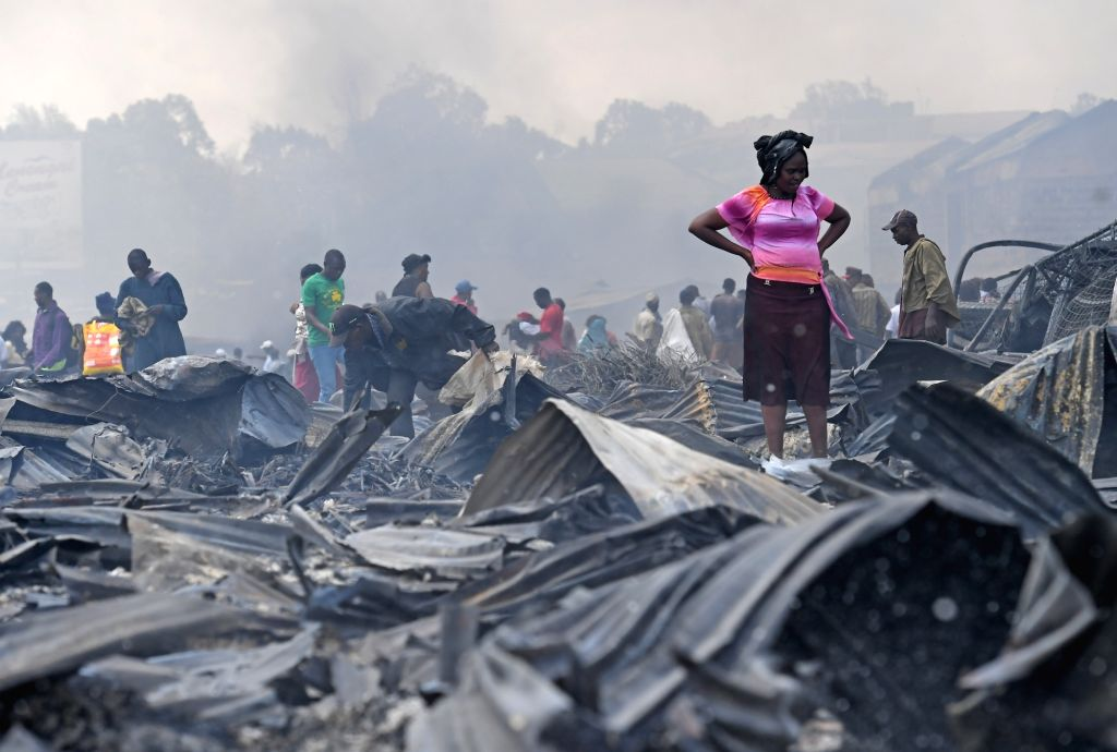 NAIROBI, Oct. 6, 2017 - People are seen at the destroyed Gikomba market in Nairobi, Kenya, Oct. 6, 2017. Kenya's largest open air market, Gikomba, located in downtown Nairobi was on Friday dawn razed ...