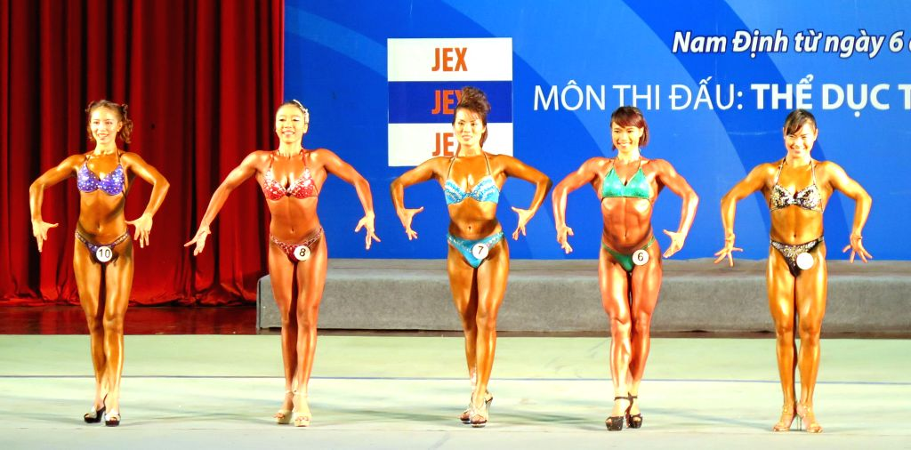 Nam Dinh: Body-builders perform during the seventh Vietnam's National Sports Games 2014 in Nam Dinh province, Vietnam, Dec. 3, 2014. The National Sports Games held every four years will start from ...