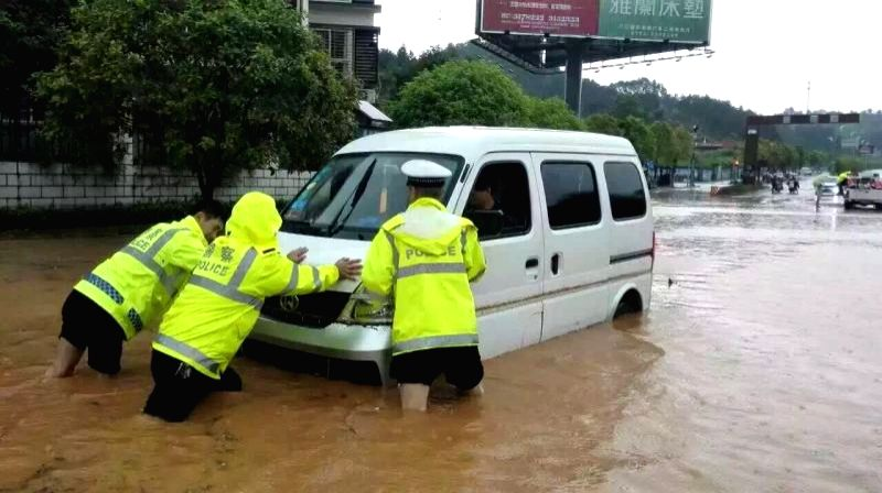 NANCHANG, May 6, 2016 - Policemen push a trapped car at the Mingyueshan scenic spot in Yichun, east China's Jiangxi Province, May 6, 2016. Mountain torrents hit the scenic zone and Wentang Town on ...