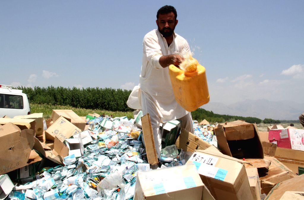An Afghan man pours petrol over expired medicine and food in Nangarhar province in eastern Afghanistan on Aug. 9, 2014. Around 150 tons of expired medicine and ...