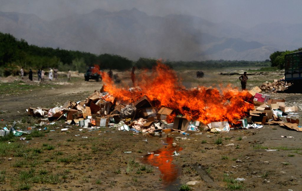 Expired medicine and food is burnt in Nangarhar province in eastern Afghanistan on Aug. 9, 2014. Around 150 tons of expired medicine and food collected from ...