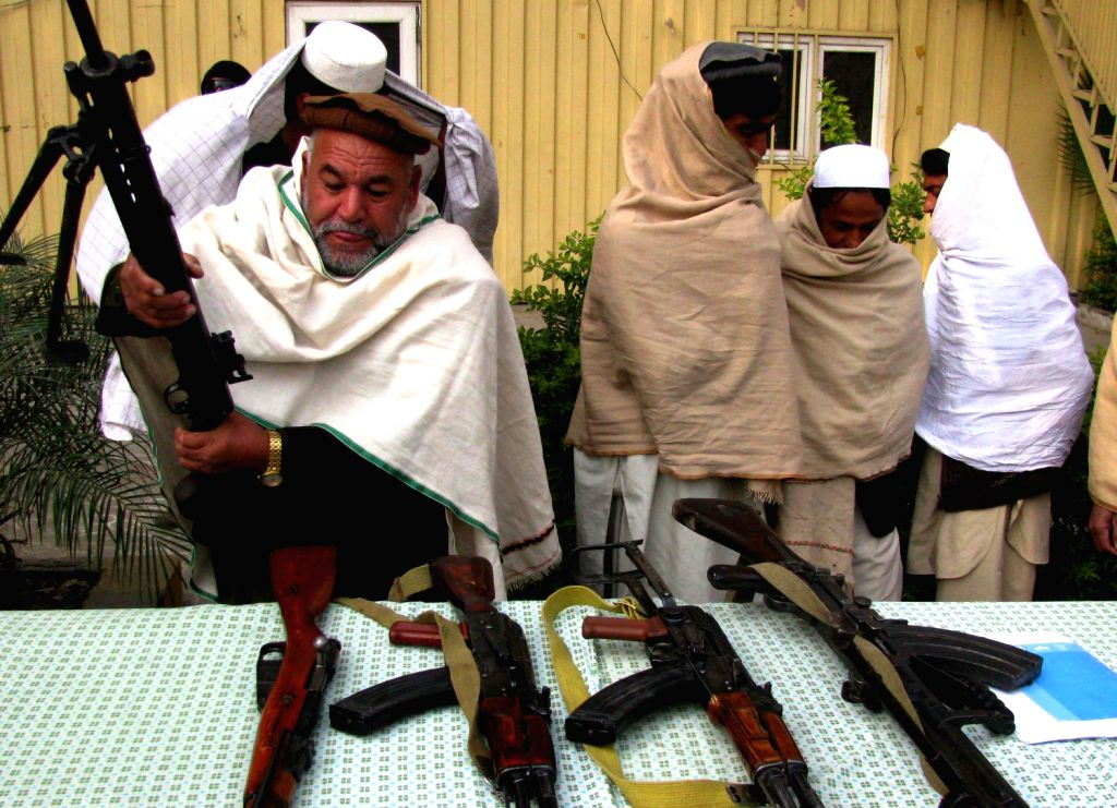 Taliban fighters attend a surrender ceremony in Nangarhar province in eastern Afghanistan on Dec. 21, 2013. Seven Taliban militants gave up fighting and ...