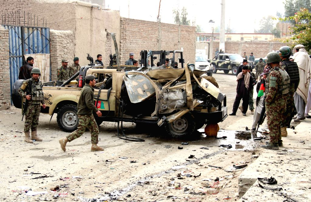 Afghan security forces gather around a destroyed military vehicle following a blast in Nangarhar province in east Afghanistan on Dec. 21, 2014. Earlier on Sunday,