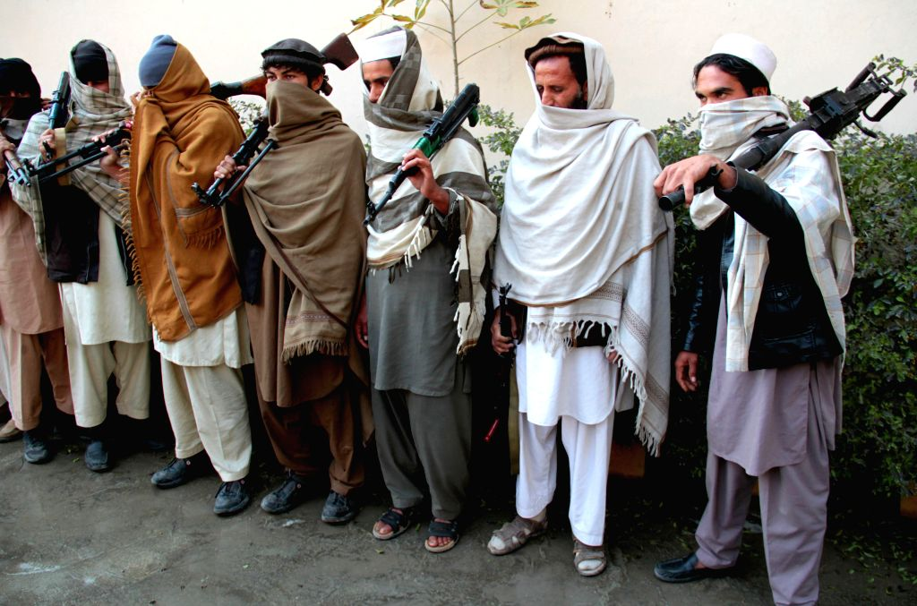 Taliban fighters attend a surrender ceremony in Nangarhar province, eastern Afghanistan, Feb. 8, 2015. A total of 20 armed militants laid down arms and gave up ...