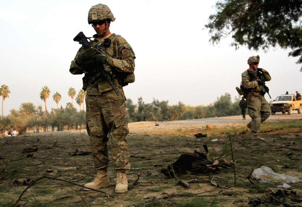 U.S. soldiers stand guard at the site of car bombing in Nangarhar Province, east Afghanistan, Jan. 5, 2015. A suicide car bomb targeted a military convoy in the ...