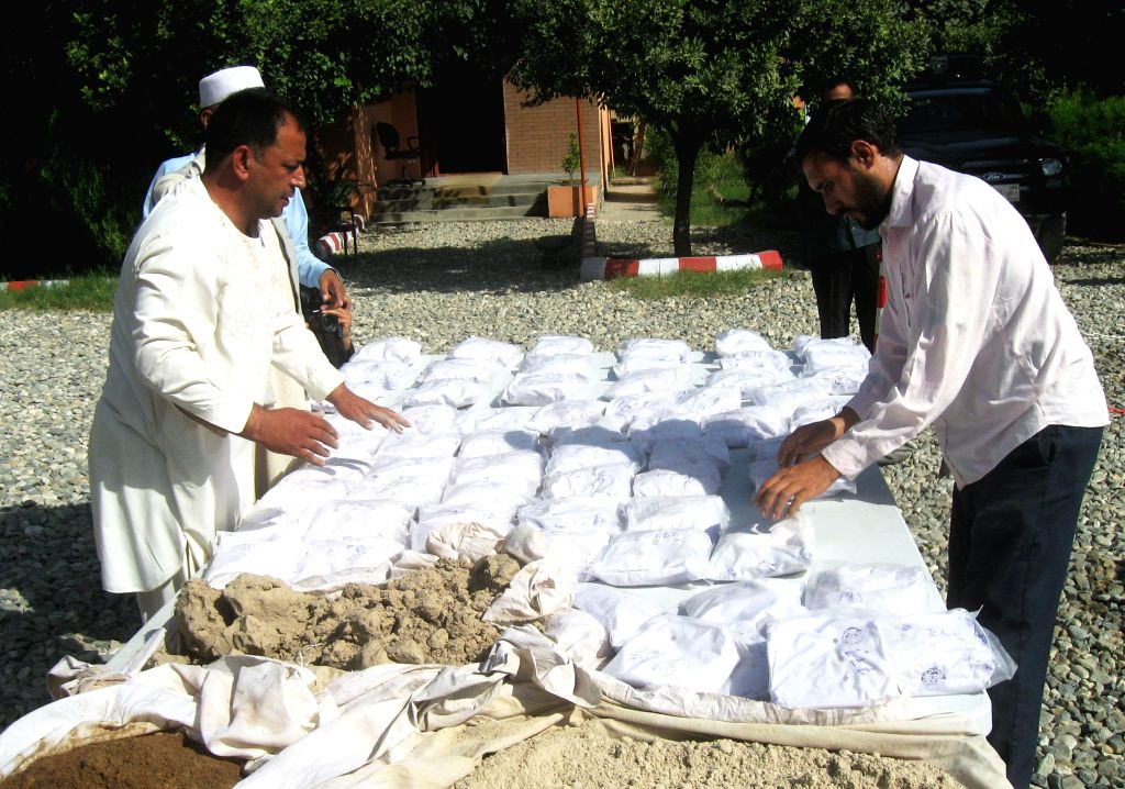 NANGARHAR, Sept. 19, 2013 (Xinhua/IANS) -- Afghan policemen display heroin at a police station in Nangarhar province of eastern Afghanistan on Sept. 19, 2013. Afghan police captured around 110 kg of heroins and detained one drug smuggler during an op