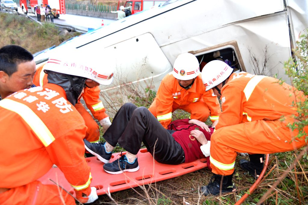 A rescuer carries an injured woman off the accident site on the Chuxiong-Dali expressway in Nanhua County, southwest China's Yunnan Province, April 6, 2015. A coach ...