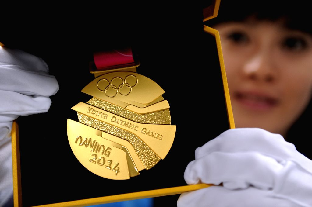 A staff from NOC shows the gold medal of 2014  Nanjing Youth Olympic Games in Nanjing, east China's Jiangsu Province, August 13, 2014.