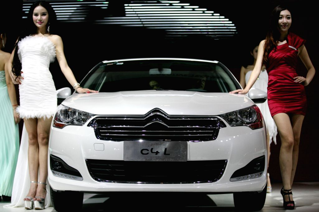 Models present a car during the 2013 Nanjing Auto Expo in Nanjing, capital of east China's Jiangsu Province, Aug. 16, 2013. The five-day event kicked off .
