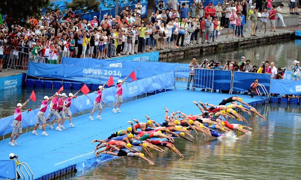 Athletes dive into the water during the men's final of triathlon event at the 2014 Nanjing Youth Olympic Games in Nanjing, east China's Jiangsu Province, on August .