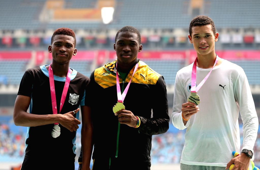 Gold medalist Martin Manley (C) of Jamaica, silver medalist Karabo Sibanda (L) of Botswana and bronze medalist Henry Delauze of Bahamas pose on the podium during ..