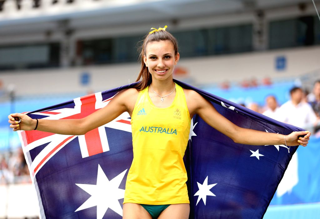 Silver medalist Tay-Leiha Clark of Australia holding her national flag, celebrates after the Women?s Triple Jump Final of athletics event at the Nanjing 2014 Youth