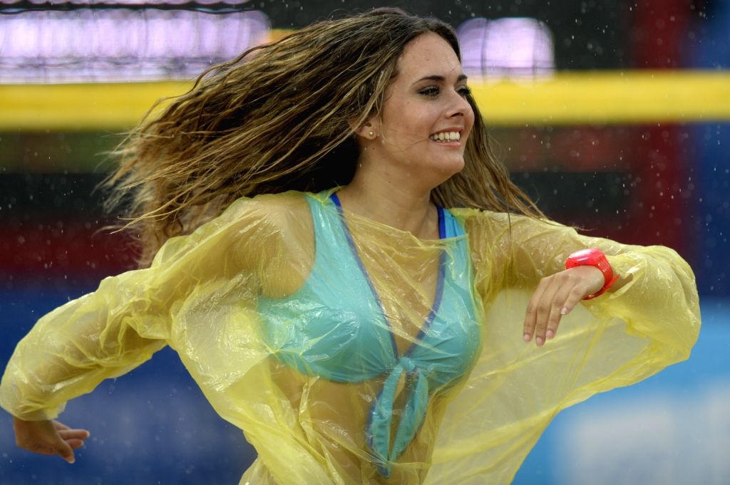 Cheerleaders of Spain dances in the rain during the men's semifinal of beach volleyball competition at Nanjing 2014 Youth Olympic Games in Nanjing, capital of east .