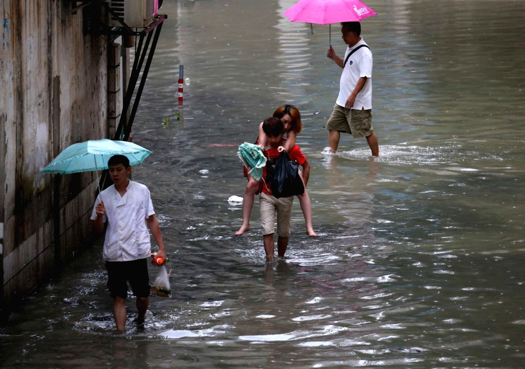NANNING, June 4, 2016 - Citizens walk on a waterlogged road in Nanning, south China's Guangxi Zhuang Autonomous Region, June 4, 2016. Local meteorological authority has issued red alerts against ...