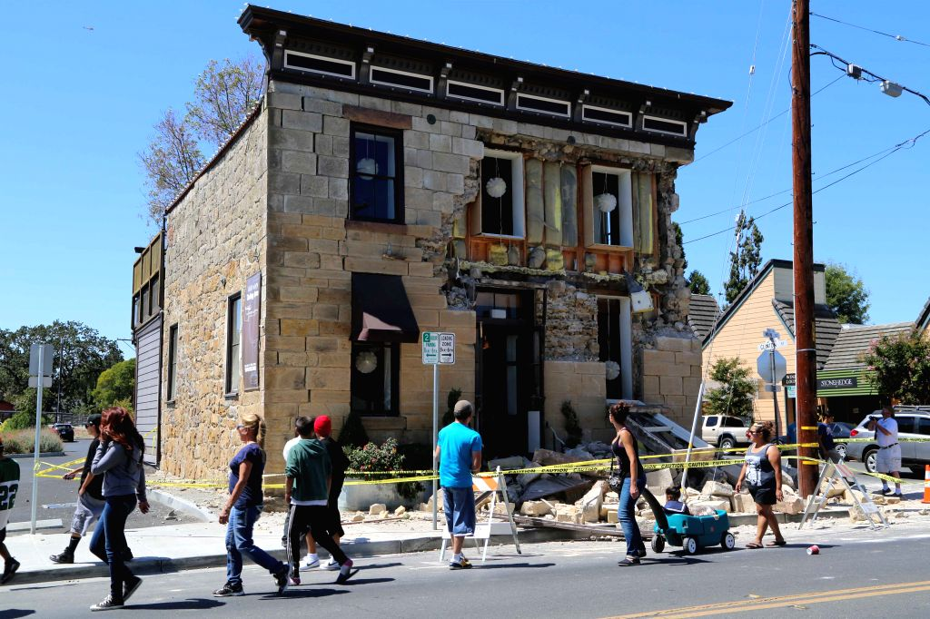NAPA (U.S.), Aug. 25, 2014 People walk past a building damaged in an earthquake in Napa, the U.S., Aug. 24, 2014. An earthquake with preliminary magnitude of 6.0 that hit northern ...