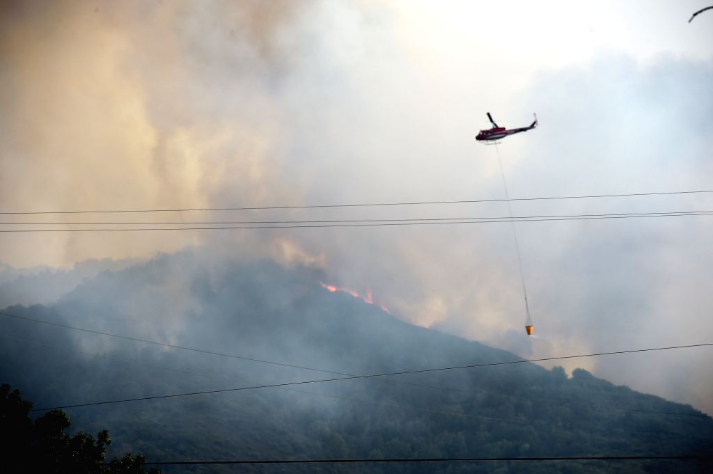NAPA VALLEY (U.S.), Oct. 11, 2017 A helicopter tries to put out the wildfire in California's Napa, the United States, on Oct. 10, 2017. The death toll has risen to 15 in north California ...