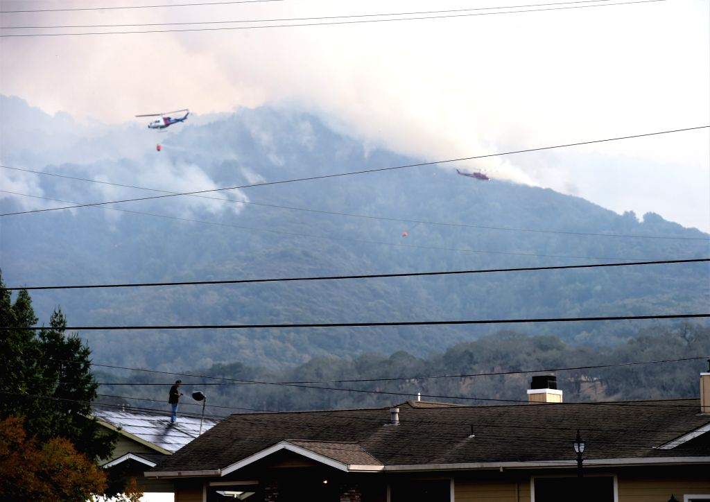 NAPA VALLEY (U.S.), Oct. 11, 2017 Helicopters try to put out the wildfire in California's Napa, the United States, on Oct. 10, 2017. The death toll has risen to 15 in north California ...