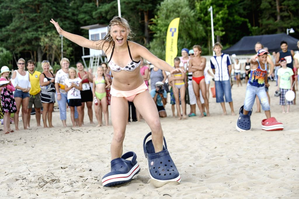 NARVA-A girl runs with giant shoes at the beach of Narva-Joesuu, Estonia, on Aug. 1, 2014.