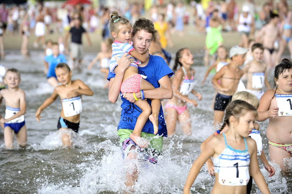 NARVA-Local people run into the sea for the Sea Mile Cross, a kind of summer beach game, at the beach of Narva-Joesuu, Estonia, on Aug. 1, 2014. (Xinhua/Sergei ...