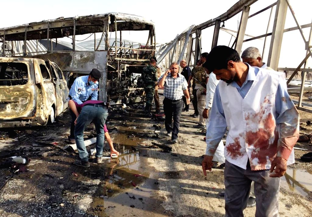 NASRIYAH, Sept. 14, 2017 - People stand beside at the site of the attacks in west of the city of Nasriyah, in Iraq's southern province of Dhi Qar, Sept. 14, 2017. Up to 50 people were killed and some ...