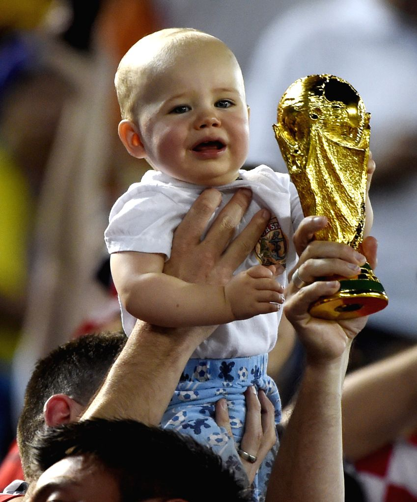 A baby held by fans of U.S. reacts during a Group G match between Ghana and U.S. of 2014 FIFA World Cup at the Estadio das Dunas Stadium in Natal, Brazil, June 16, ...