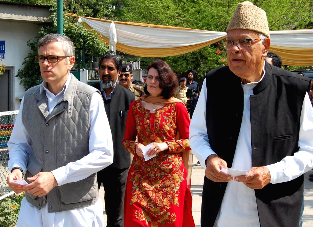 National Conference president and Union minister Farooq Abdullah and Jammu and Kashmir Chief Minister Omar Abdullah arrive at a polling booth to cast their votes in Srinagar on April 30, 2014.