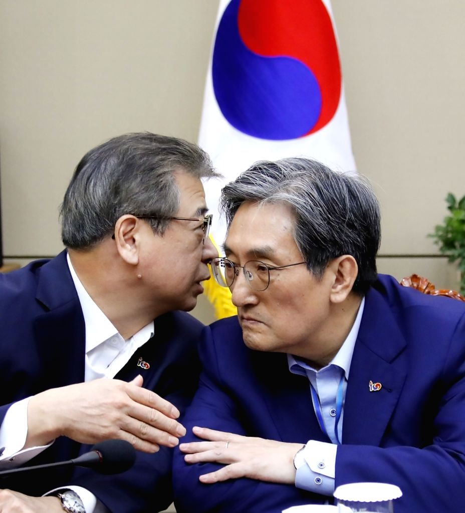 National Intelligence Service chief Suh Hoon (L) speaks privately with presidential chief of staff Noh Young-min before the National Security Council meeting begins at the presidential office ...