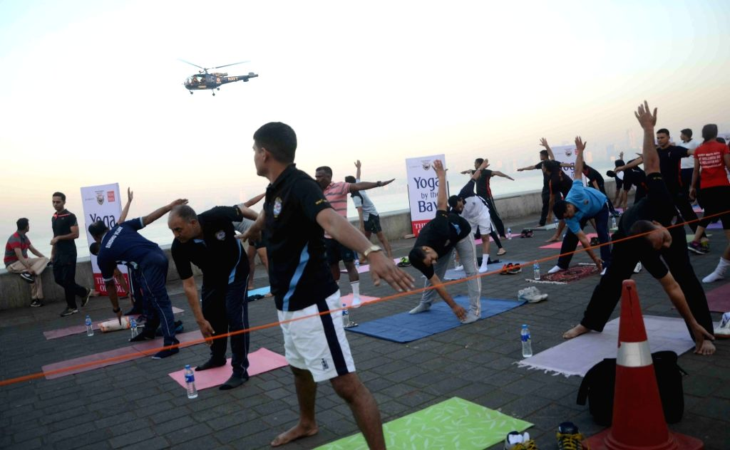 """Navy-men participate in """"Yoga by the Bay"""" at Marine Drive in Mumbai on Nov 27, 2016."""