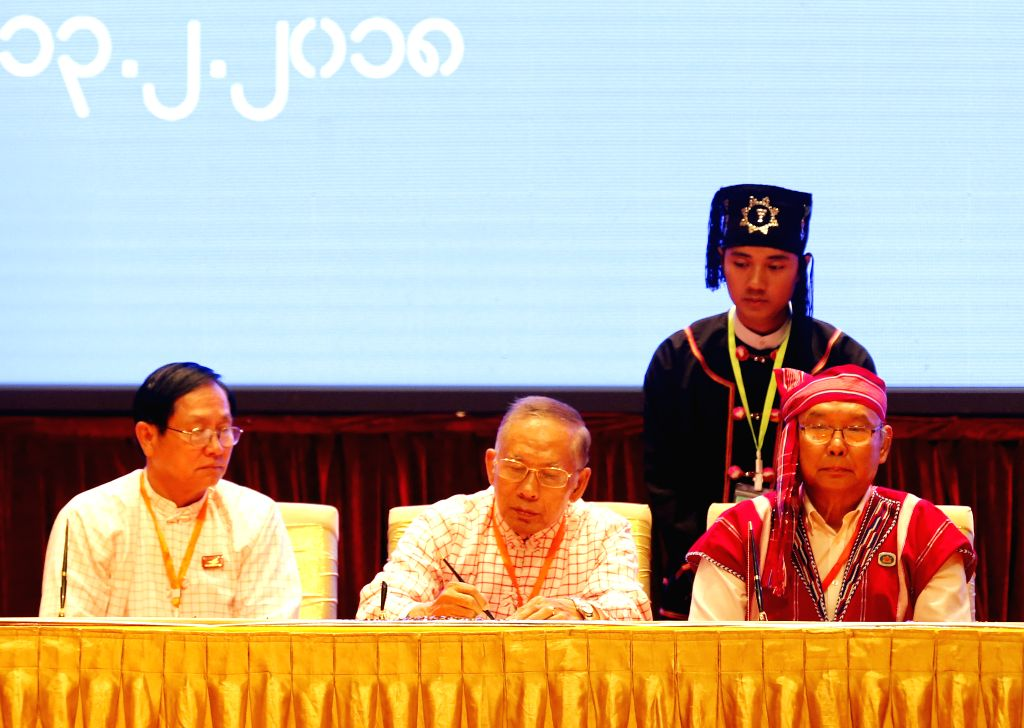 NAY PYI TAW, Feb. 13, 2018 - New Mon State Party (NMSP) chairman Nai Htaw Mon (C), signs documents during the signing ceremony of Nationwide Ceasefire Accord at the Myanmar International Convention ...