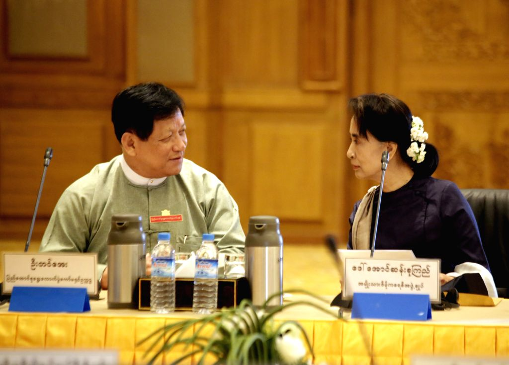 Aung San Suu Kyi (R), leader of Myanmar's National League for Democracy, talks with Chairman of the Union Election Commission U Tin Aye (L) before the meeting ..