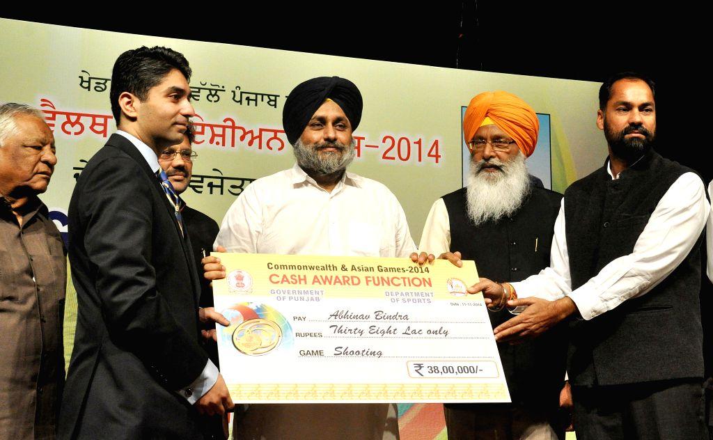 Punjab Deputy Chief Minister Sukhbir Singh Badal felicitates shooter Abhinav Bindra during Asian and Commonwealth medal winners award ceremony in Chandigarh on Nov 11, 2014. - Sukhbir Singh Badal