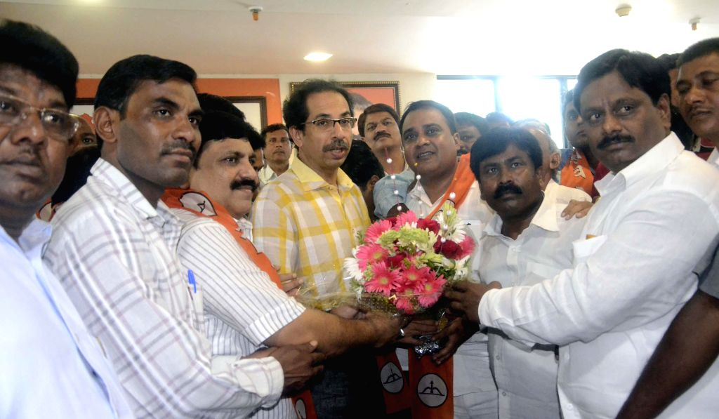 NCP leader Kishor Kanhere and his supporters join Shiv Sena chief Uddhav Thackeray in Mumbai on July 14, 2014.