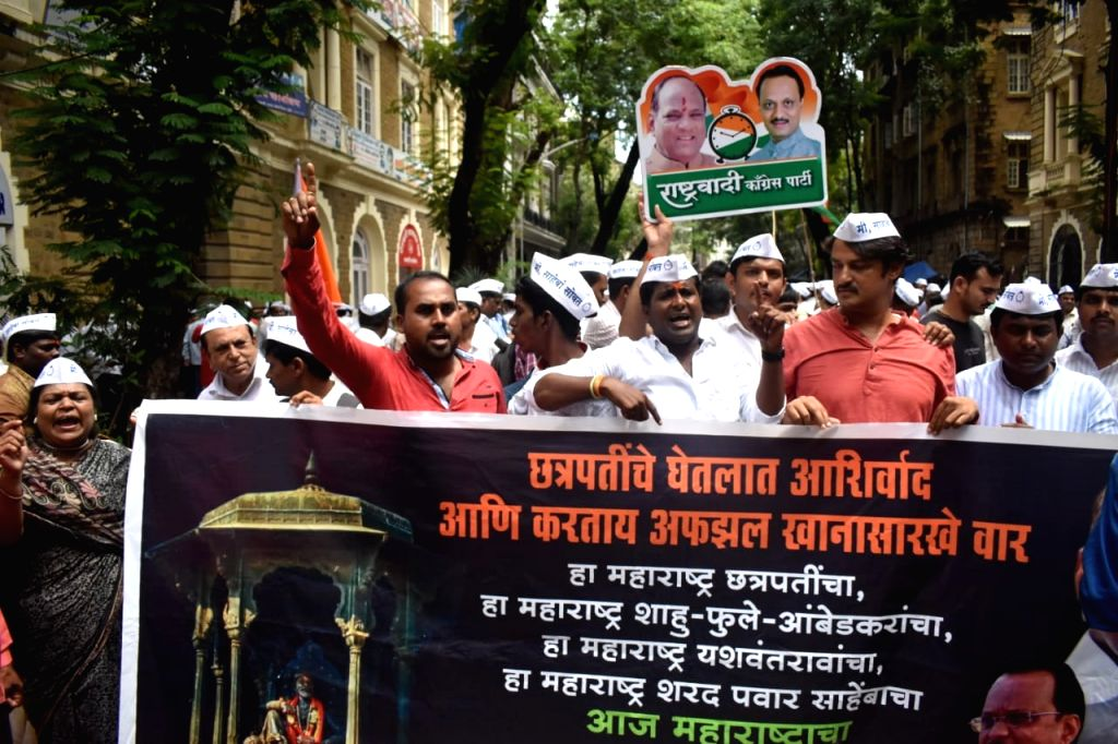 NCP workers and leaders gather at the Enforcement Directorate (ED) office to express solidarity with party President Sharad Pawar who prepared to appear before the ED, in Mumbai on Sep 27, ...