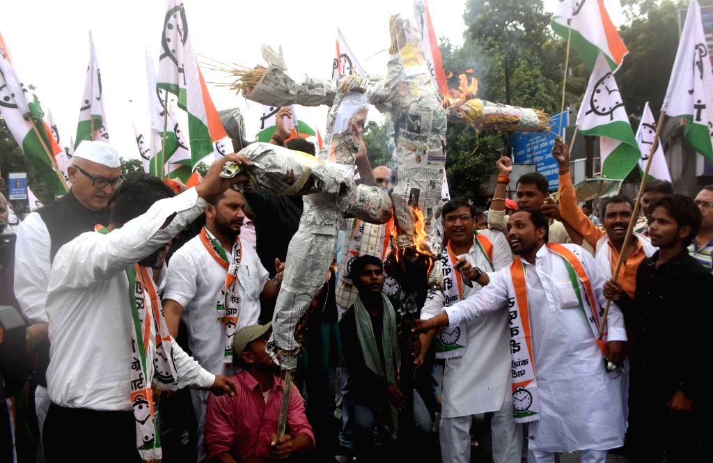 NCP workers burn the effigies of Prime Minister Narendra Modi and Union Home Minister Amit Shah as they protest against the Enforcement Directorate for naming Sharad Pawar in a money ... - Narendra Modi and Amit Shah