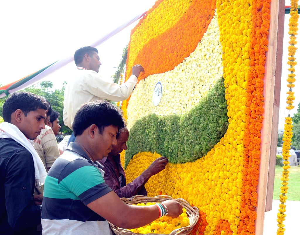 NDMC workers busy making Indian flag using flowers on the eve of 68th Independence Day in New Delhi on Aug 14, 2014.