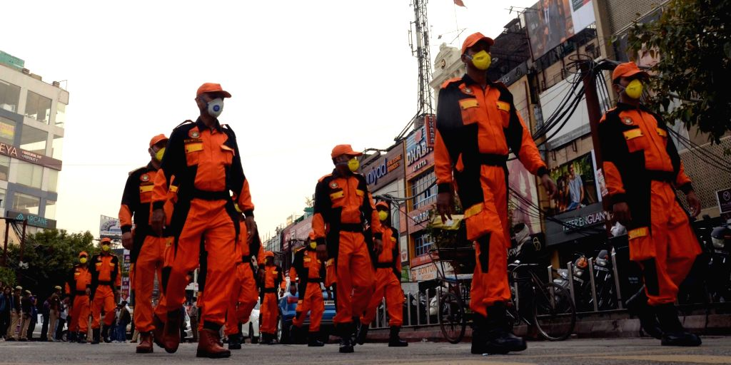 NDRF personnel conduct a flag march creating awareness among people on COVID-19 ahead of Sunday's nationwide 'Janata Curfew' imposed in the wake of increasing cases of coronavirus, in Noida ...