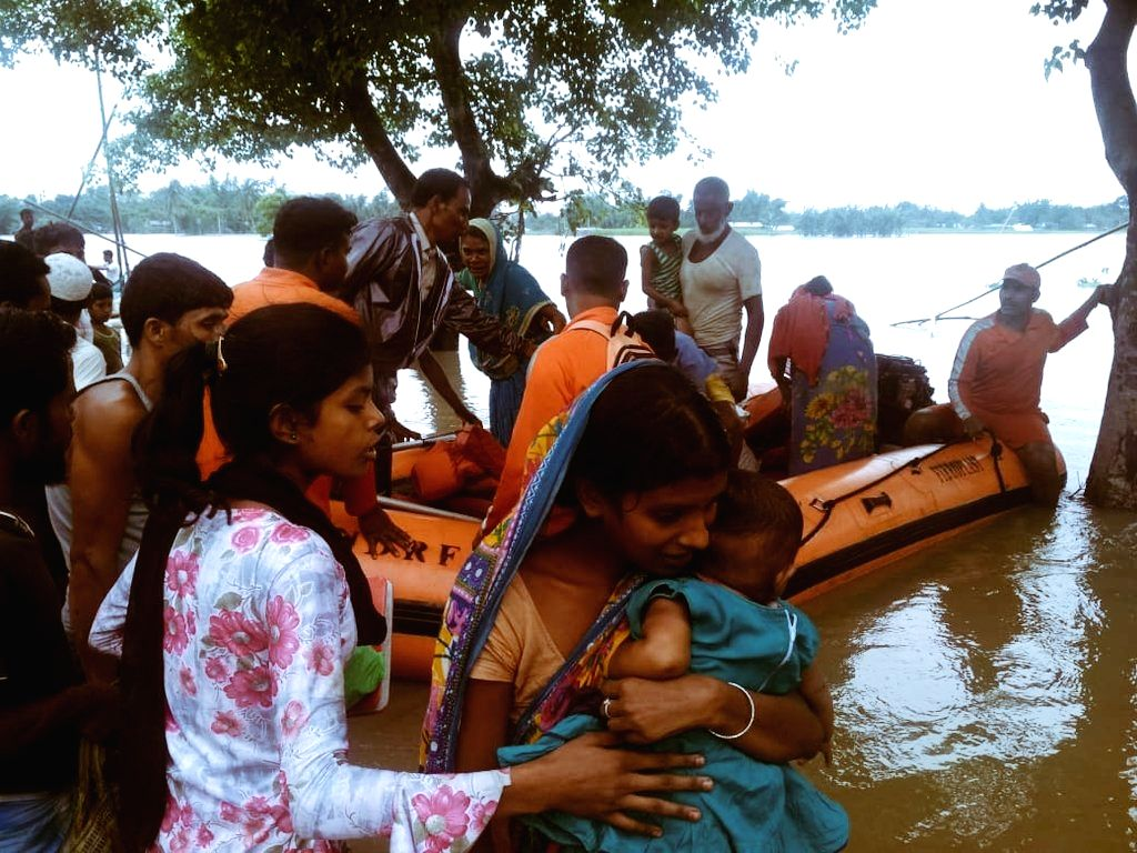 NDRF personnel conduct evacuation drive at Laharighat in Assam's flood affected Marigaon district, on July 16, 2019.