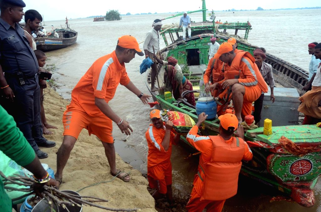 NDRF personnel on a boat with rescued flood victims from Nakta Diara near Danapur in Patna District of Bihar on Aug 22, 2016. (Photo: IANS)