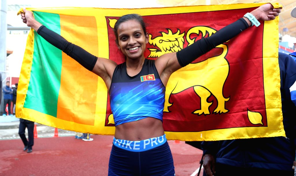 NEPAL, Dec. 7, 2019 - Hurina Kesara Wijayaratne of Sri Lanka poses with National flag after winning Gold medal during women's marathon at 13th South Asian Games in Kathmandu, Nepal, Dec. 7, 2019.