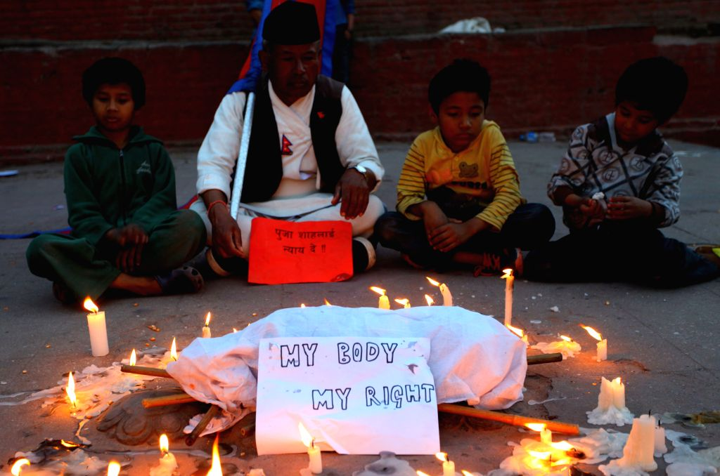 Nepalese people sit around the body of a six-year-old girl who was reportedly raped in her village a few days ago in Kathmandu, Nepal, March 11, 2015. (Xinhua/Sunil ...